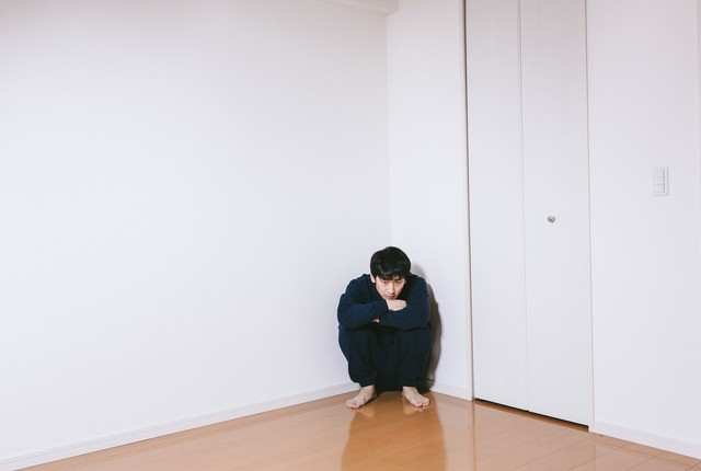 部屋の隅でうずくまる男性